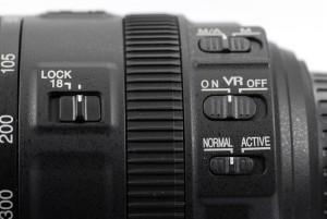 Zoomarretierung links (LOCK), Fokusmodusschalter (MA), Bildstabilisator (VR) und Bildstabilisator-Modusschalter